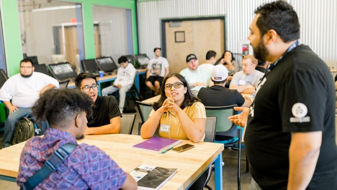 San Joaquin County Office of Education/CodeStack coordinator and software engineer Jateen Bhakta, right, speaks with students attending the accelerated coding school in Stockton.