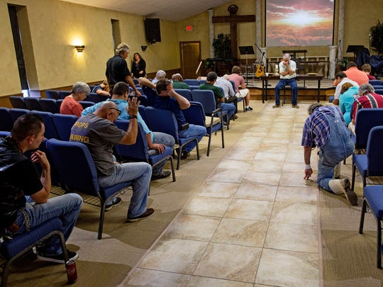 Pastor Mark Carroll leads prayer at South Walker Baptist Church. The church, led by Pineville HIgh Schhol and Louisiana College graduate Carroll, has become a shelter and food distribution point for the community since the recent flooding.