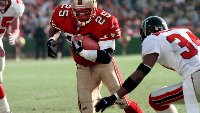 San Francisco 49ers running back Charlie Garner runs for an 8-yard touchdown in front of Atlanta Falcons cornerback Ray Buchanan, right, and defensive tackle Shane Dronett, left, in the first quarter in San Francisco, Sunday, Dec. 12, 1999. (AP Photo/Paul Sakuma)