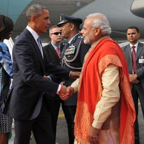 Indian Prime Minister Narendra Modi and President Obama shake hands as the president and First Lady Michelle Obama arrive in New Delhi.