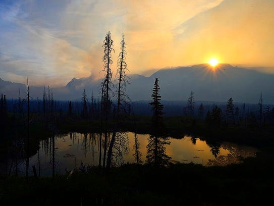 The sun sets over St. Mary and the Reynolds Creek Fire