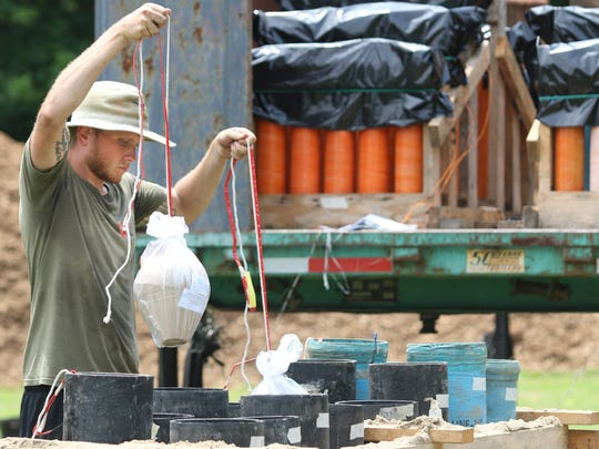 A Pyro Shows worker puts shells into position as the