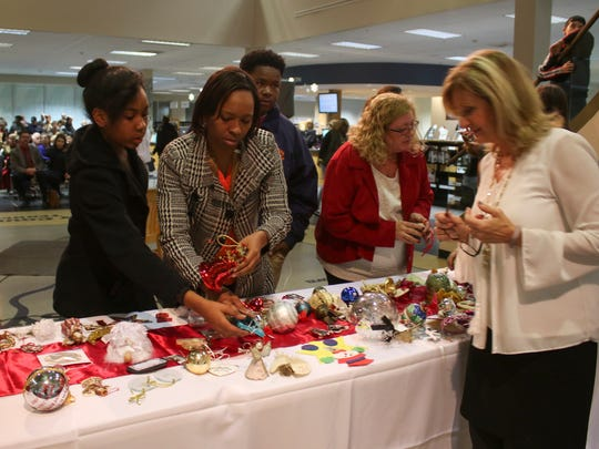 Family members and friends of homicide victims pick up their ornaments before Wings of Love held at the Clarksville-Montgomery Public Library on Wednesday. There were 423 victims honored at the event.