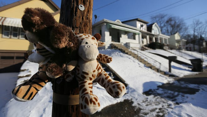A makeshift memorial sits outside the house where police say Georta Mack was shot and killed by his father.
