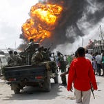 Somali soldiers on patrol pass a market fire in the capital Mogadishu on Tuesday.