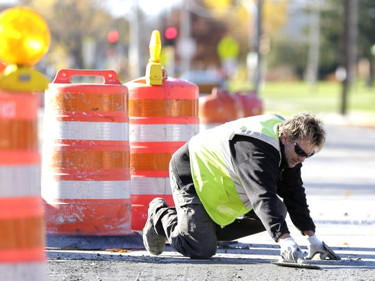 Sommers Construction Co. crew member Thomas Schoelzel smooths out freshly poured concrete at North Fisk and Kellogg streets on Nov. 10 in Green Bay.