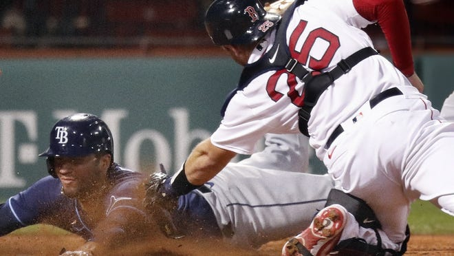 Boston Red Sox catcher Kevin Plawecki (right) tags out Tampa Bay Rays' Michael Perez trying to score on a double by Austin Meadows during the fourth inning of a game on Monday in Boston.
