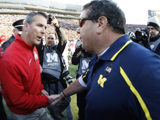 Ohio State coach Urban Meyer and Michigan coach Brady Hoke shake hands after Ohio State's 42-41 win in Ann Arbor on November 30, 2013.