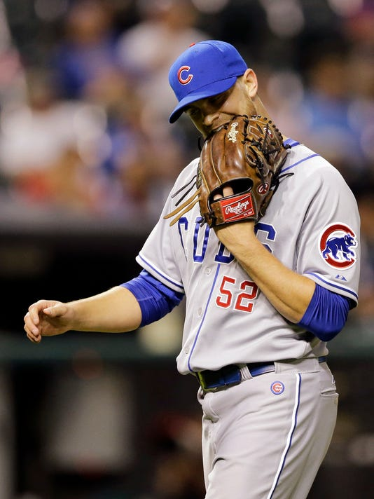 Chicago Cubs relief pitcher Justin Grimm bites his mitt as he walks to the dugout during the seventh inning of a baseball game against the Cleveland Indians, Thursday, June 18, 2015, in Cleveland. Grimm gave up an RBI single to Giovanny Urshela in the inning. (AP Photo/Tony Dejak)