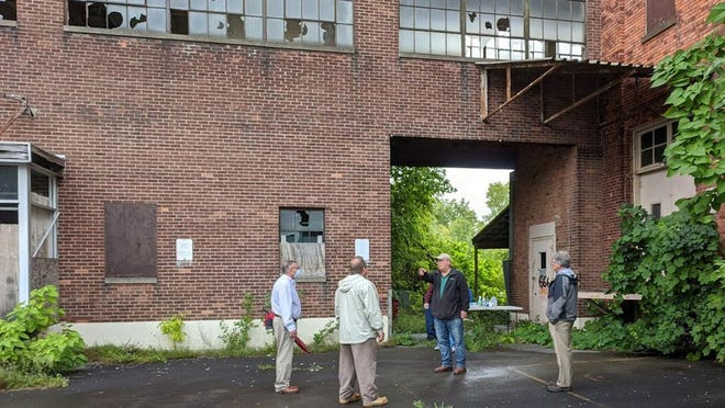 Ilion Mayor Brian Lamica, second from right, speaks to (from left to right) Assemblyman Brian Miller, Herkimer County Industrial Development Agency Executive Director John Piseck and Tom Seguljic, an environmental engineering consultant from HRP Associates, last week at the Duofold site in Ilion.