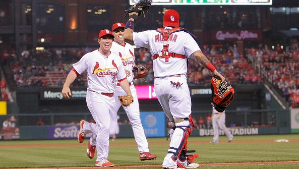 Jedd Gyorko, left, congratulates Yadier Molina, right after Molina's snap throw caught Eugenio Suarez at third to end the sixth inning of Friday's 7-5 Cardinals victory over the Reds.