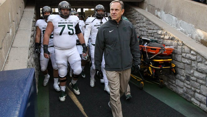 Michigan State head coach Mark Dantonio leads his team out of the tunnel prior to the Spartans' season-finale at Penn State. The Spartans are facing off-field turmoil coming off a 3-9 season.