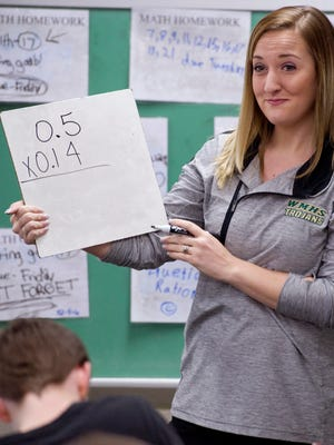 Oakland City Elementary School teacher Lauren Schmidt leads a lesson on working with decimals and fractions in Caleb Cherry's sixth grade class.