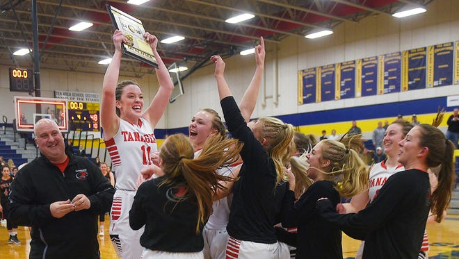 Vermillion's Haleigh Melstad lifts the award plaque into the air after their win against Dell Rapids Thursday, March 1, at Tea Area High School in Tea.
