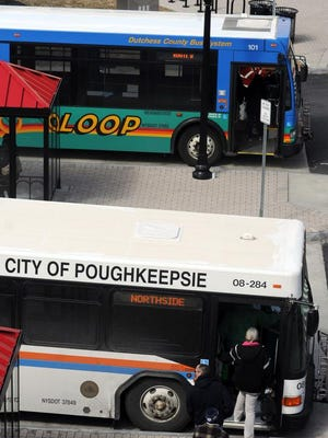 In this 2014 file photo, a City of Poughkeepsie bus, below, and a Dutchess County LOOP bus, above, drop off and pick up riders at the transit hub in the City of Poughkeepsie.