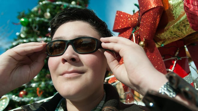 Caleb Longwell, 12, tries on his new pair of glasses in Mesilla, N.M. on Saturday which help correct for the colorblindness he has experienced all of his life. Longwell won a free pair of perscription glasses in a nationwide contest sponcered by EnChroma and Clorox.