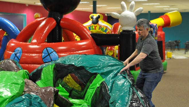 Slinkee's owner Phil Fuselier and staff air inflatables Friday afternoon before reopening.