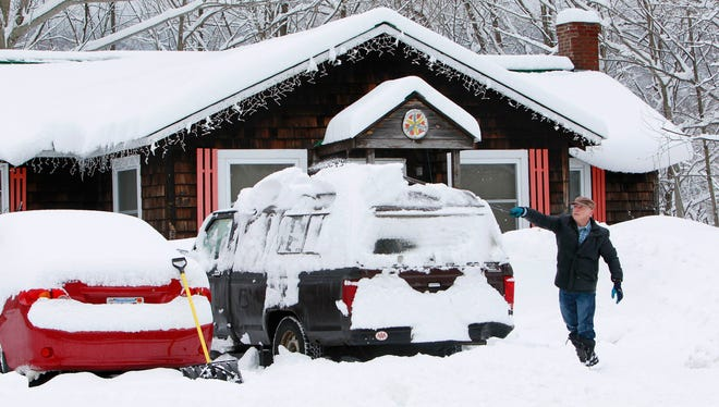 Donald Croteau works to clear nearly a foot of snow off his car on the first day of spring, Thursday, March 20, 2014, in North Woodstock, N.H. More snow is forecast for New England on Tuesday and Wednesday.
