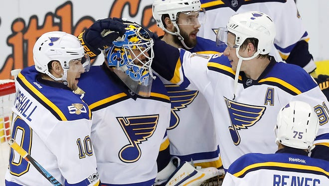 St. Louis Blues goalie Carter Hutton, second from left, celebrates a 2-0 win against the Detroit Red Wings after an NHL hockey game Wednesday, Feb. 15, 2017, in Detroit. (AP Photo/Paul Sancya)