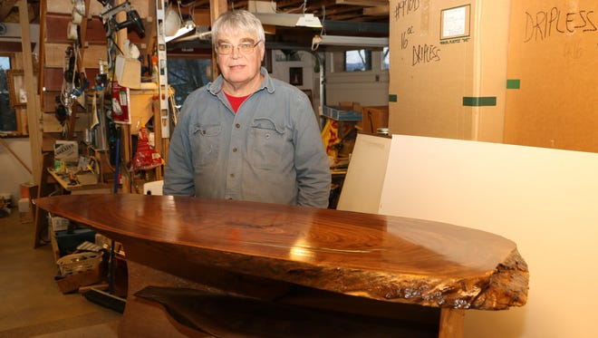 Marwin Cummings is shown with the coffee table he made from a 19-inch-wide,4-foot-long slab of walnut. It is one of three tables he will have on display at the Gmeiner.