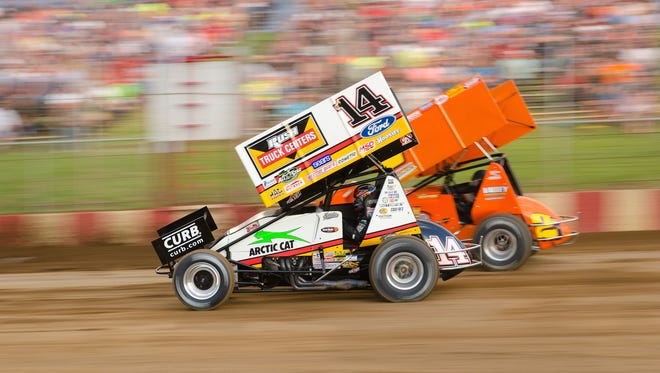 Three-time NASCAR champion Tony Stewart (14) passes local driver Scott Neitzel en route to  a heat race victory at the Interstate Racing Association sprint-car event Thursday, June 8, 2017, at Angell Park Speedway in Sun Prairie, Wis.