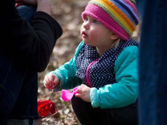 Two-year-old Juniper Anderson looks to her mother,
