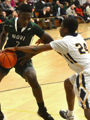 Novi's Traveon Maddox, Jr., (left) tries to retain possession of the ball guard by Walled Lake Central's Runako Ziegler in Monday's Class A regional semifinal at West Bloomfield.