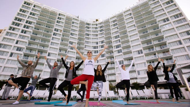 In this Jan. 24, 2016, photo, Paula Walker, center foreground, an instructor with Green Monkey Yoga, leads a yoga class at the Mondrian South Beach Hotel in Miami Beach, Fla.