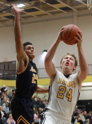 Hendersonville's Drew Hohenbrink drives as Northeast's Alec Kegler looms above on Tues. Nov. 14, 2017.  Photo by Dave Cardaciotto