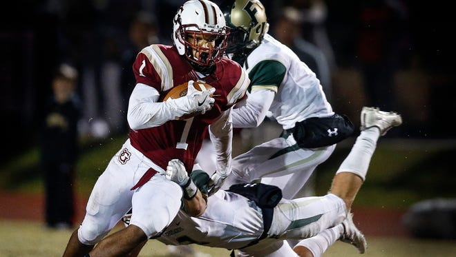St. George's receiver Corey Jones (front) scrambles past First Assembly Christian School defenders to complete a touchdown reception during second-half action of their quarterfinals playoff game.