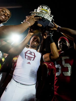 Troy players hoist the champions trophy after defeating Ohio in the Dollar General Bowl at Ladd-Peebles Stadium in Mobile, Ala. on Friday December 23, 2016.