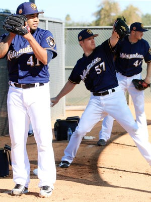 Brewers pitchers Junior Guerra (from left), Chase Anderson and Corey Knebel throw in the bullpen Wednesday, the first day of spring-training drills for pitchers and catchers.