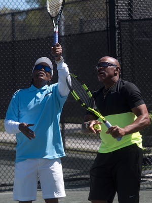 Local tennis pro Linsley McMillion, right, gives pointers to Parris Watt while the two men practice Thursday, March 22, 2018, at the Roger Scott Tennis Center in Pensacola.