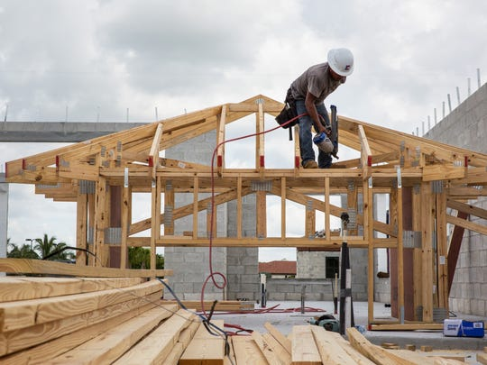 A constructions worker builds the framework for a home