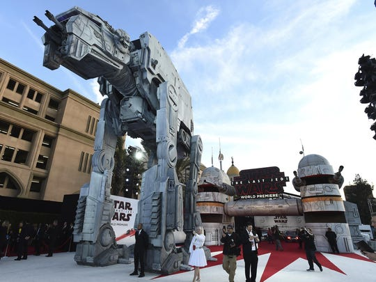 A massive AT-M6 walker towers over the white and red