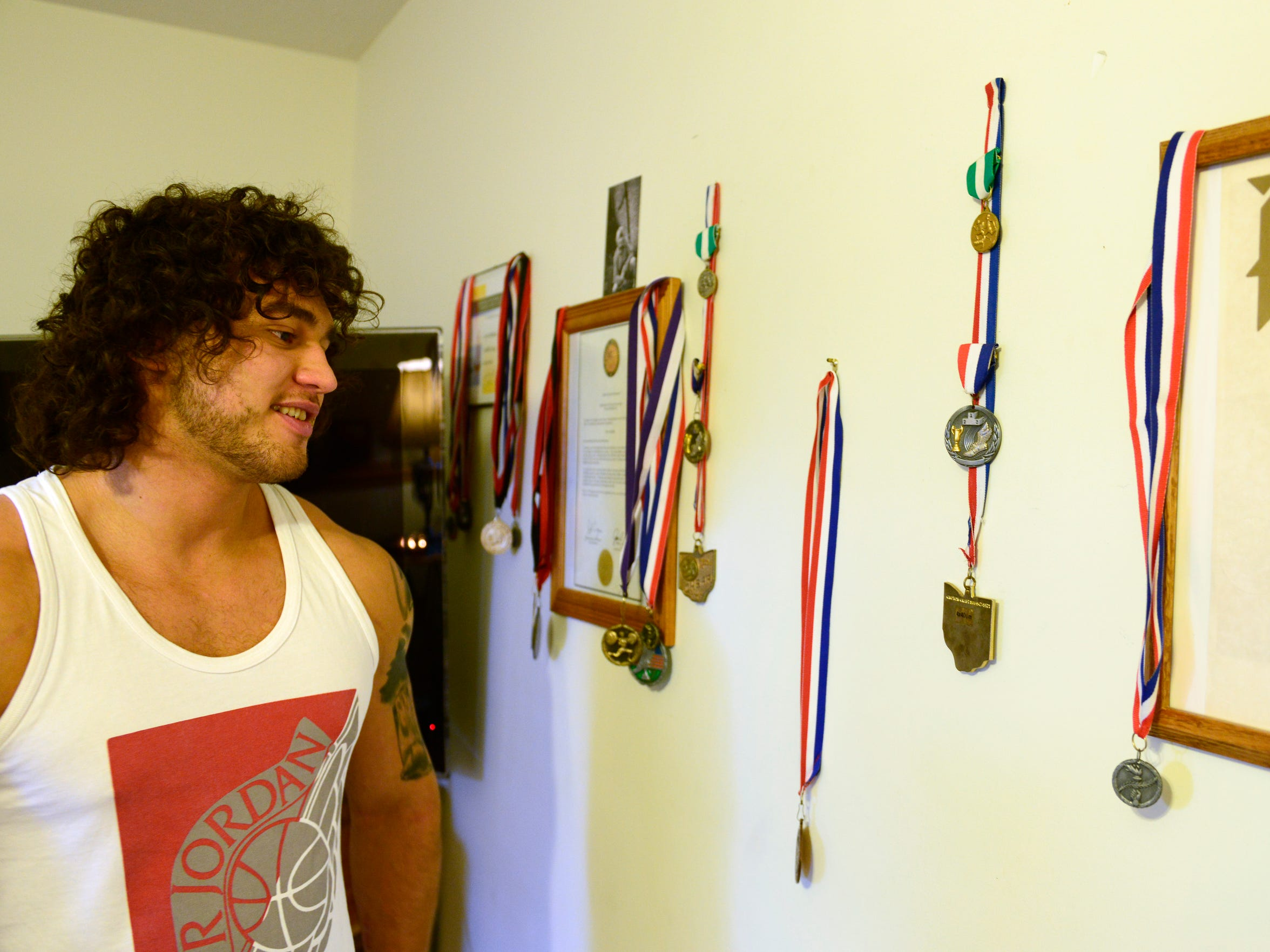 Richie Webber looks at the medals he won at the state high school track championship, and for other sports, hanging on the wall in his home. He had opportunities for college scholarships, but lost them because he failed a school drug test and was kicked off the team.