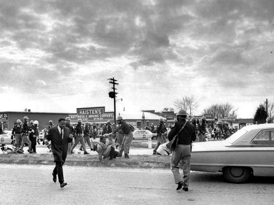 """On March 7, 1965, John Lewis, center, of the Student Nonviolent Coordinating Committee, is forced to the ground as state troopers break up the demonstration on what has become known as """"Bloody Sunday"""" in Selma, Ala."""