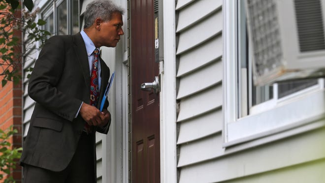 Rochester School District Superintendent Bolgen Vargas approaches an apartment building during a recent attendance blitz, where he and others visited the homes of chronically absent students to help alert families of resources that may help prevent kids from missing school.