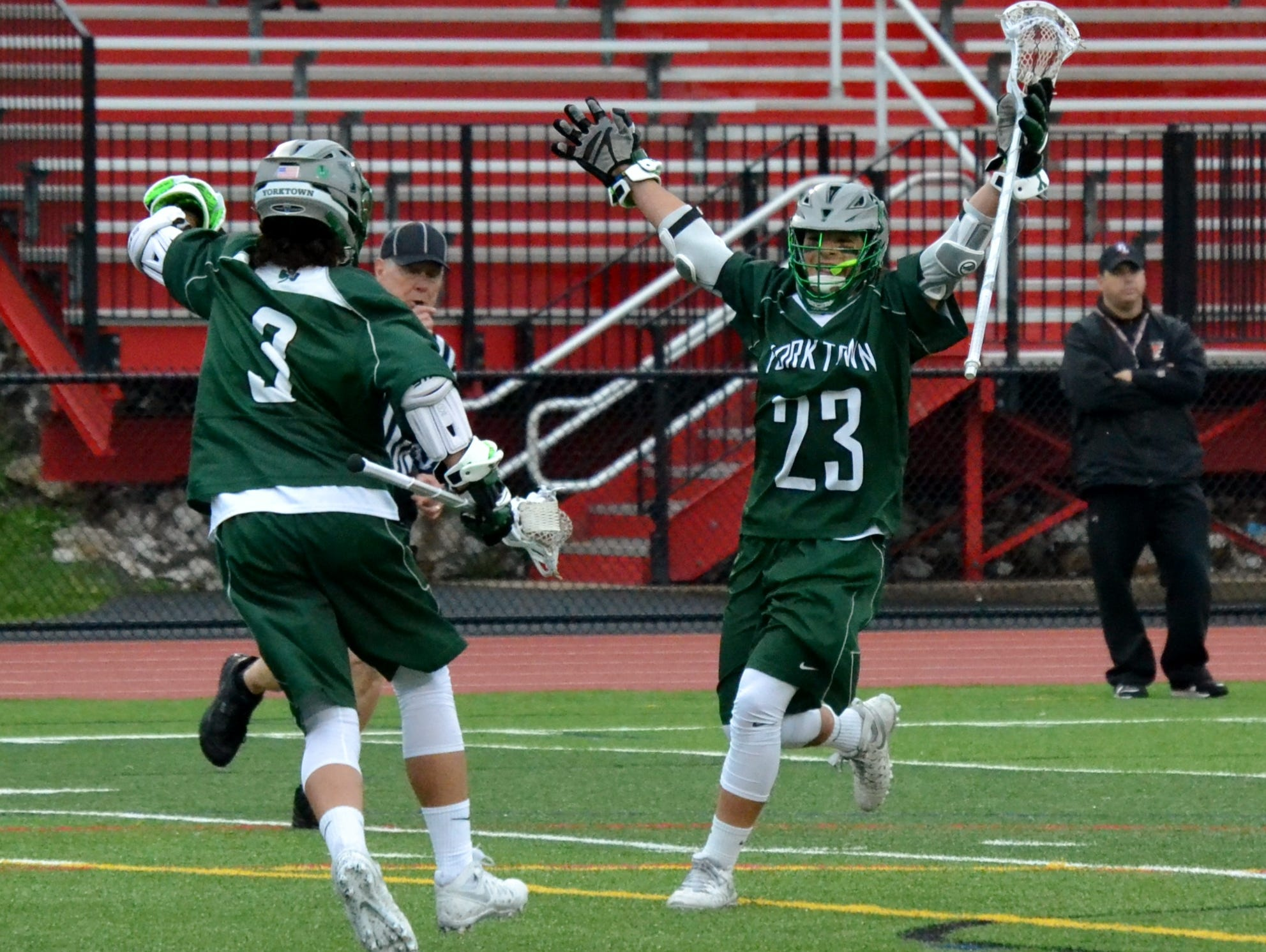 Hunter Embury (23) celebrates a third-period goal with his brother, Jamison. They each scored twice for Yorktown in an 8-6 win at Fox Lane on Thursday.