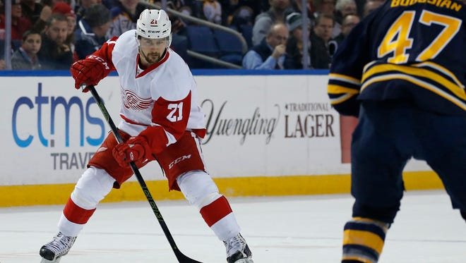 Jan 2, 2016; Buffalo, NY, USA; Detroit Red Wings left wing Tomas Tatar (21) flips the puck into the zone as Buffalo Sabres defenseman Zach Bogosian (47) defends during the first period at First Niagara Center. Mandatory Credit: Kevin Hoffman-USA TODAY Sports