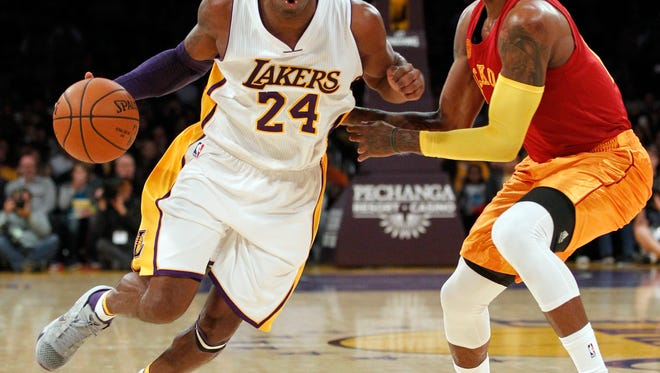 Los Angeles Lakers forward Kobe Bryant (24) drives past Indiana Pacers forward Paul George, right, on Sunday night.