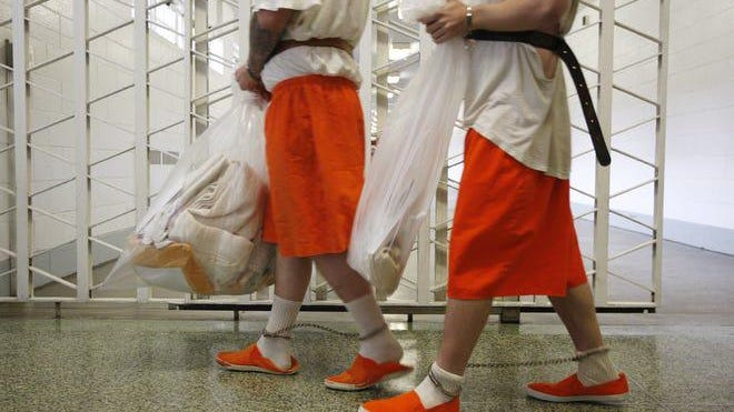 Inmates make their way down a hallway before being transported from the Lebanon Correctional Institution in 2009.