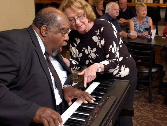 """Al Martin reacts in surprise as Liz Richbourg tells him how her grandmother taught herself to play the number he is shown playing. Martin and some of his friends are planning a """"Spring Has Sprung"""" concert Saturday night at DeVillier's Square."""
