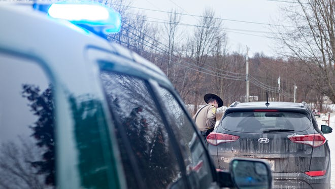 Vermont State Trooper Jay Riggen hands a ticket to a driver suspected of speeding on U.S. 7 in Swanton on Friday, Dec. 15, 2017.