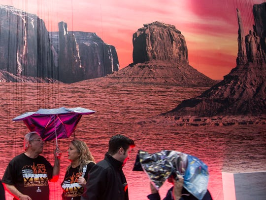 Downtown Phoenix visitors shield themselves from rain on Thursday in front of a mural of Monument Valley at Verizon Super Bowl Central. An organizer of the street fair said visitors should not despair — a massive climbing wall is the only thing that would shut down in rain.