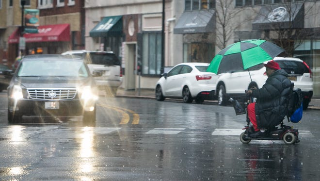 A woman crosses Delaware Aveunue in downtown Wilmington as rain moves in with a flood watch in effect through Thursday.