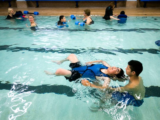 Kevin Coriano, right, helps support Ramon Arellano Hernandez as he floats through the water at the YMCA pool on Wednesday, April 27, 2016.