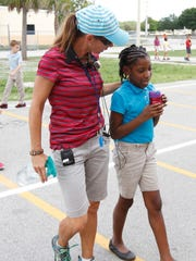 Golden Apple winner Christine Morgan speaks with student Naiysa Louis at Rayma C. Page Elementary School in Fort Myers Tuesday.
