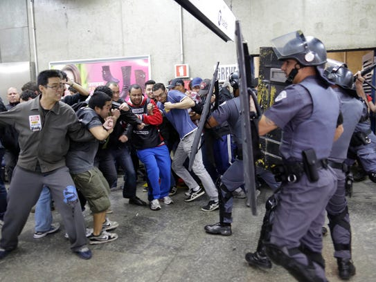 Subway train operators, along with some activists, clash with police at the Ana Rosa metro station on the second day of their metro strike in Sao Paulo, Brazil, Friday, June 6, 2014. The workers clashed with police as they tried to block other operators from breaking the strike. Overland commuter train operators went on strike Thursday, putting at risk the only means that most soccer fans will have to reach Itaquerao stadium ahead of next week's World Cup. (AP Photo/Nelson Antoine)