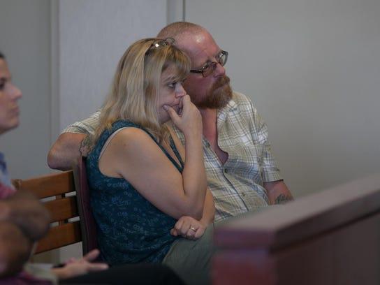 Angelina and Bruce Benoir sit behind daughter Karri
